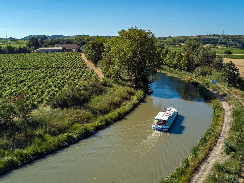 Navigation fluviale sur le canal du Midi, dans l'Aude, à travers vignes ©Jay Si, Istock